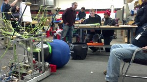 Students working on the robot to pick up a ball. We sacrificed the net to save weight for the low volume pump.